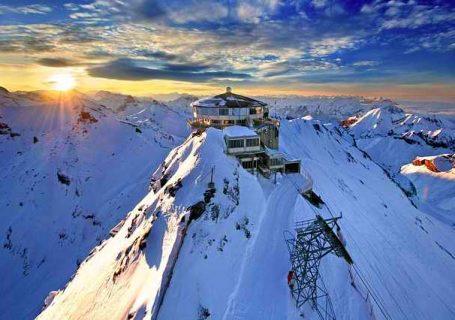 Gipfelstation auf schneebedeckten Bergkämmen, Sonnenuntergang mit dramatischem Wolkenbild