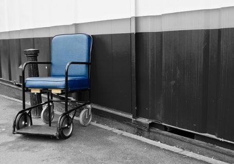 Rollstuhl, älteres, einfaches Modell auf einem Flur an der Wand stehend