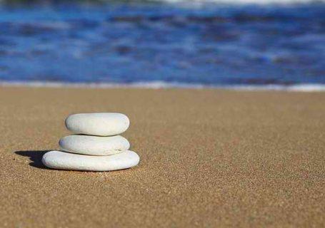 3 flache Steine als Stapel am Strand vor dem Meer im Hintergrund